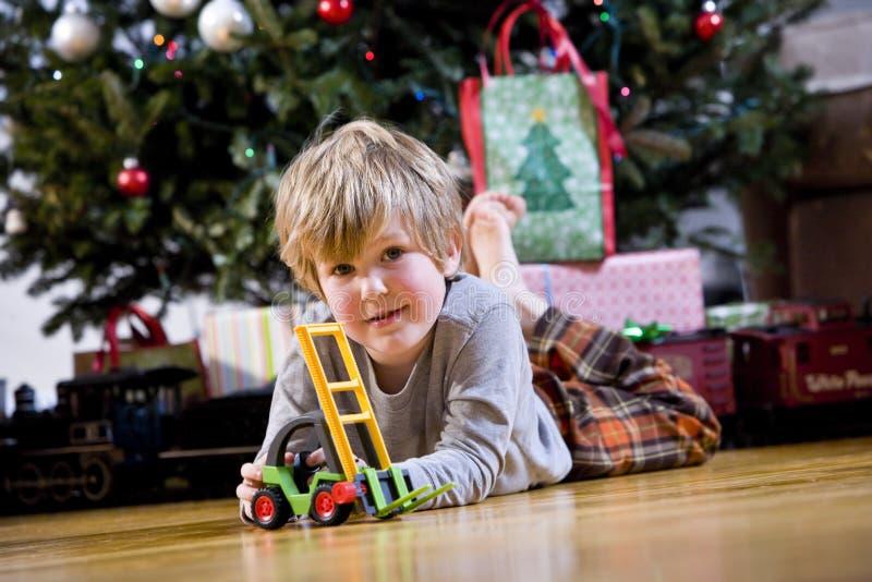 Kleiner Junge, der mit Spielzeug durch Weihnachtsbaum spielt stockfoto