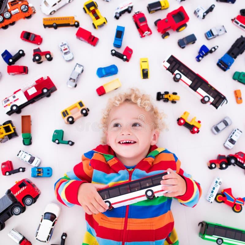 Kleiner Junge, der mit Spielzeugautos spielt lizenzfreie stockfotos