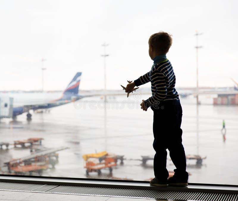 Kleiner Junge, der mit Spielzeugflugzeug im Flughafen spielt lizenzfreie stockbilder