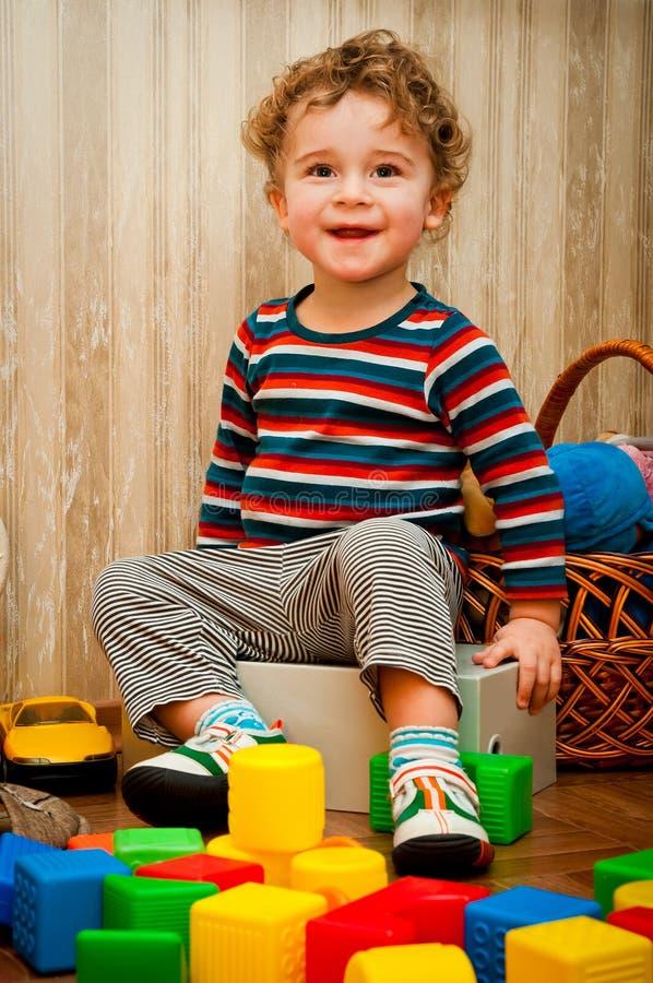 Kleiner Junge, der mit Würfeln spielt stockfotografie