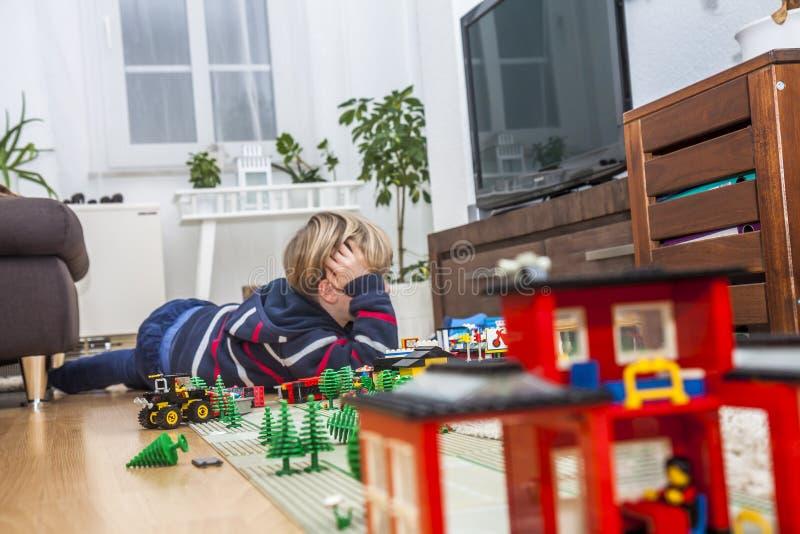 Kleiner Junge, der mit Ziegelsteinen auf dem Boden spielt lizenzfreie stockfotografie