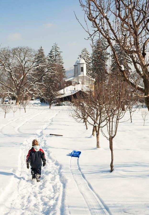 Kleiner Junge, der nach Hause auf Schnee geht stockfotos
