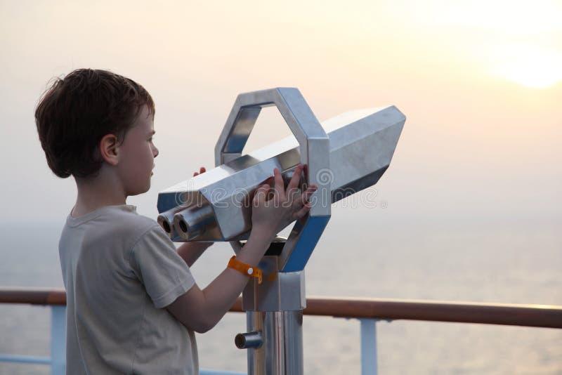 Kleiner Junge, der nahe binokularem steht lizenzfreie stockfotos