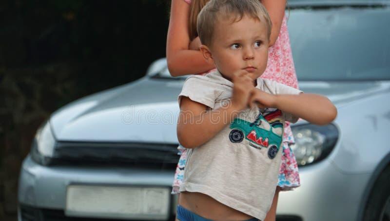 Kleiner Junge, der nahe dem Auto zur Tageszeit steht Konzept des glücklichen Lebens lizenzfreie stockbilder