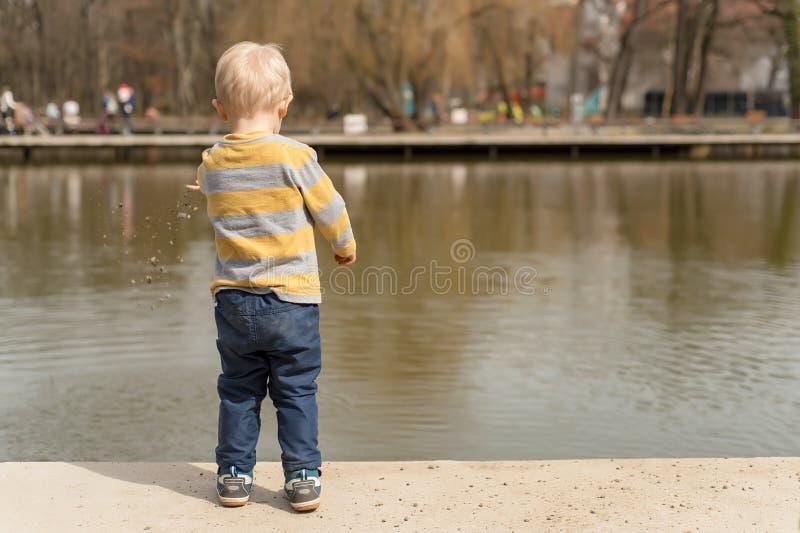 Kleiner Junge, der nahe dem See spielt stockfoto