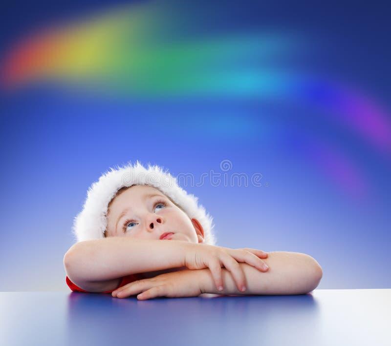 Kleiner Junge, der oben zum Regenbogen auf Himmel schaut stockfoto
