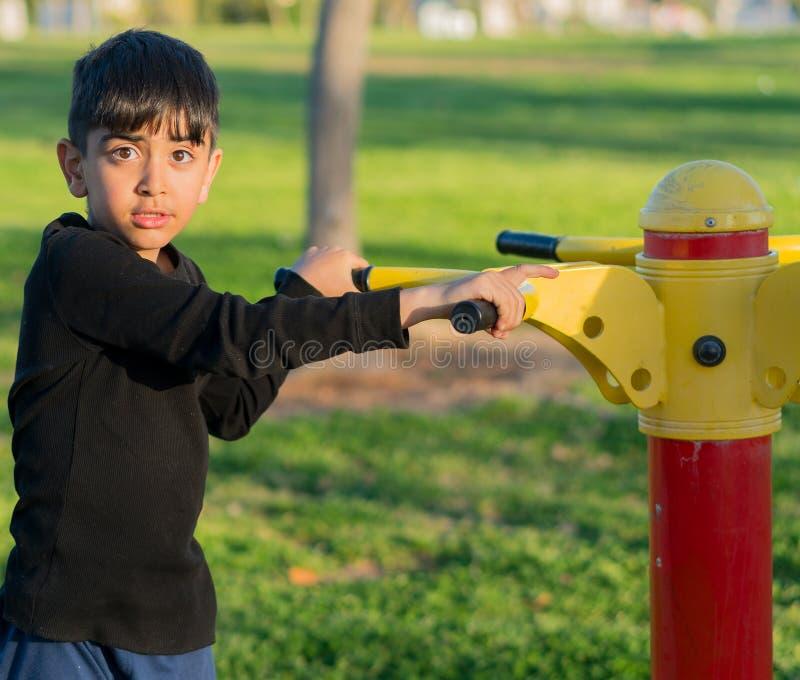 Kleiner Junge, der am Park spielt stockbild