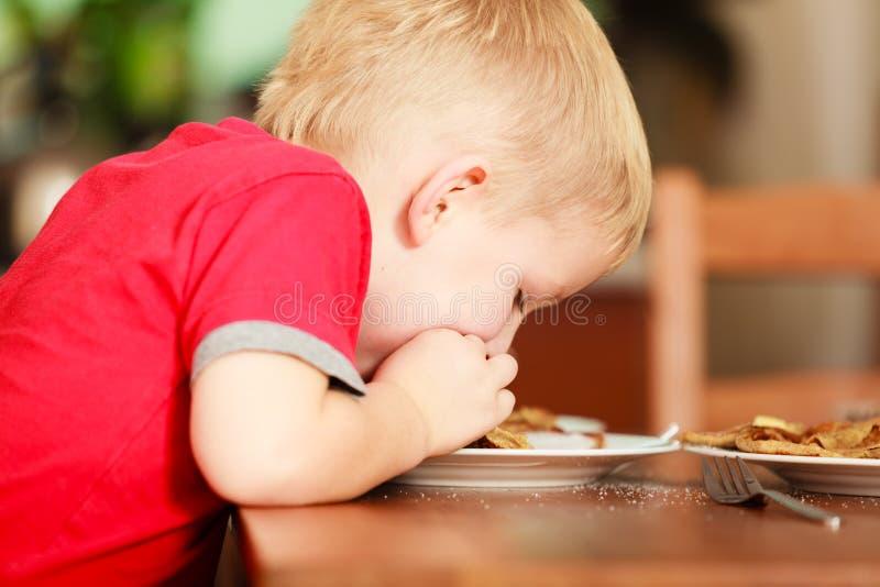 Kleiner Junge, der Pfannkuchen für breaktfast isst stockfoto