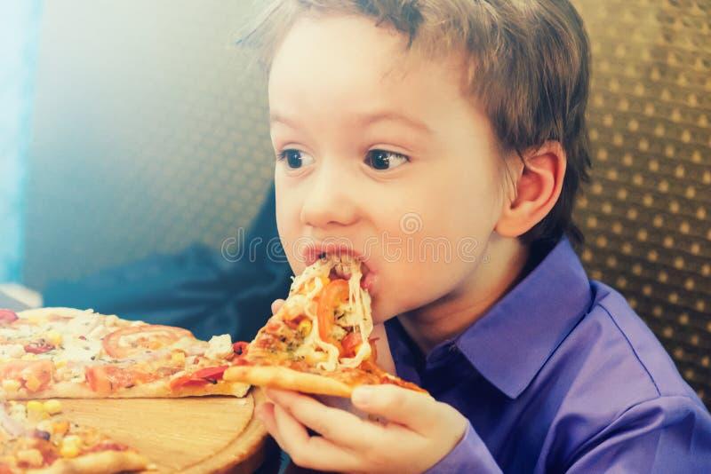 Kleiner Junge, der Pizza am Café isst stockbild