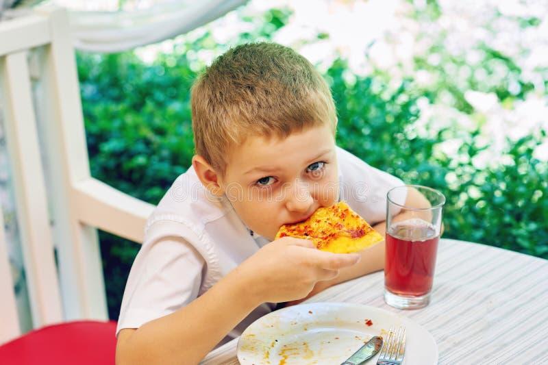 Kleiner Junge, der Pizza in einem Café isst stockfotos