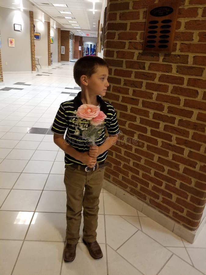 Kleiner Junge, der Rosen hält lizenzfreies stockfoto