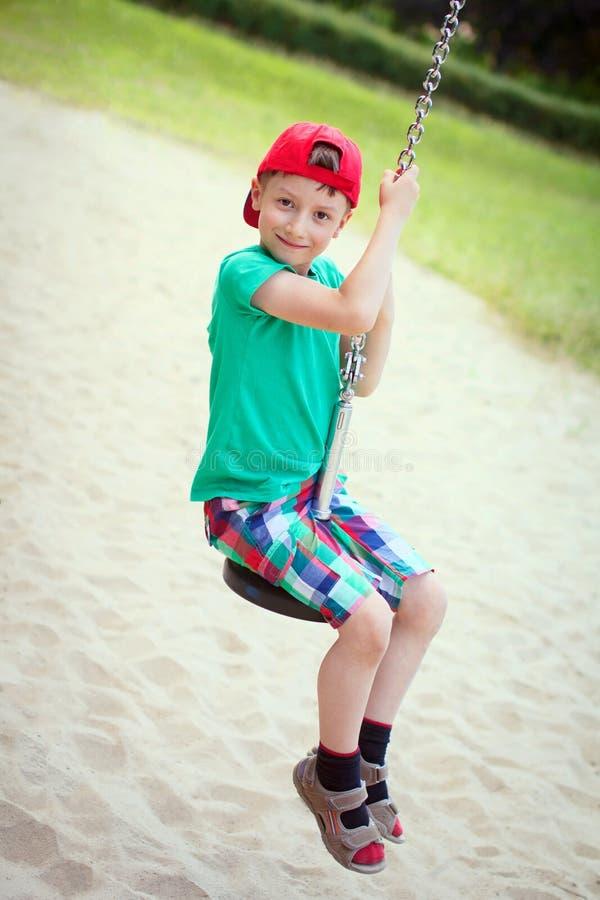 Kleiner Junge in der roten Kappe sitzen auf Schwingenseil lizenzfreies stockbild