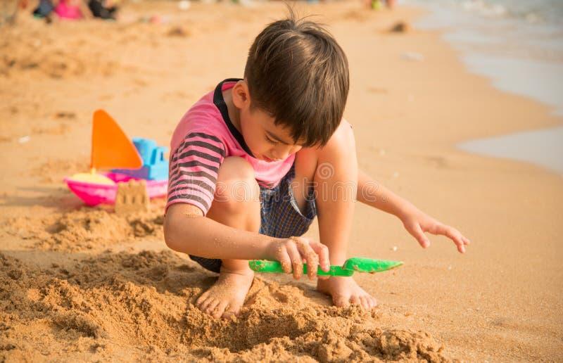Kleiner Junge, der Sand auf dem Strandsommer spielt lizenzfreie stockbilder