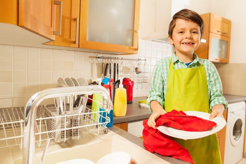Kleiner Junge, der saubere Platte in der Küche abwischt lizenzfreie stockfotografie