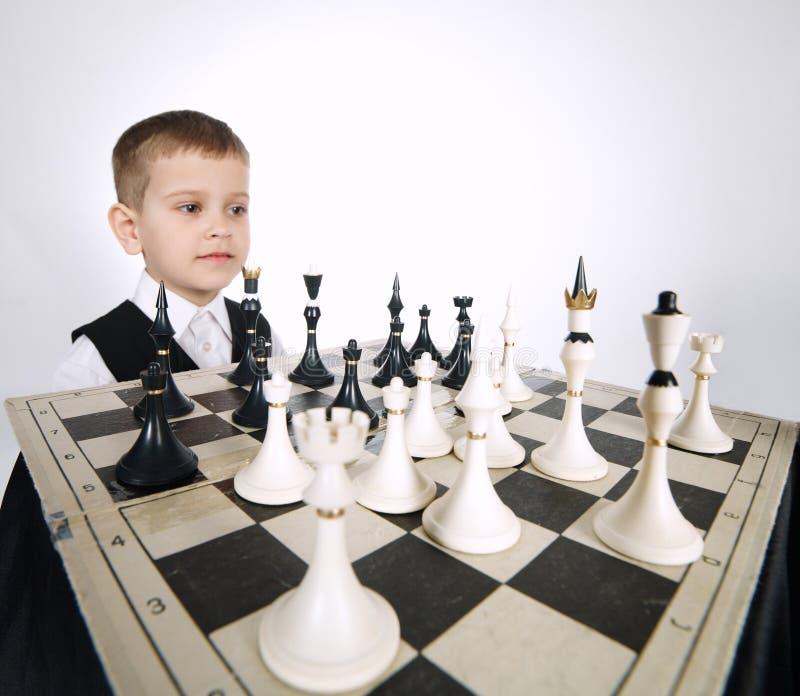 Kleiner Junge, der Schach auf Weiß spielt stockbild