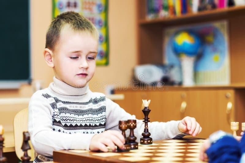 Kleiner Junge, der Schach spielt stockfoto