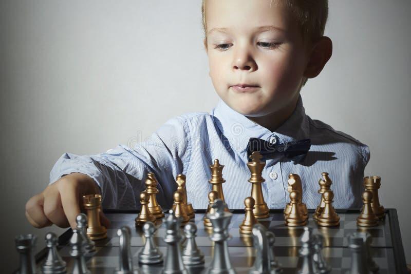 Kleiner Junge, der Schach spielt Intelligentes Kind Kleines Genie Kind Intelligentes gam lizenzfreie stockfotos