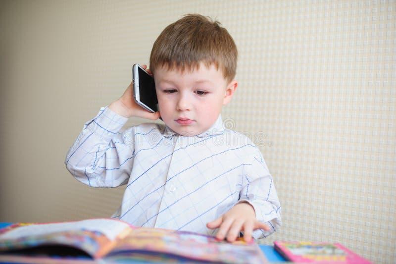 Kleiner Junge, der am Schreibtisch sitzt und am Telefon spricht lizenzfreies stockbild