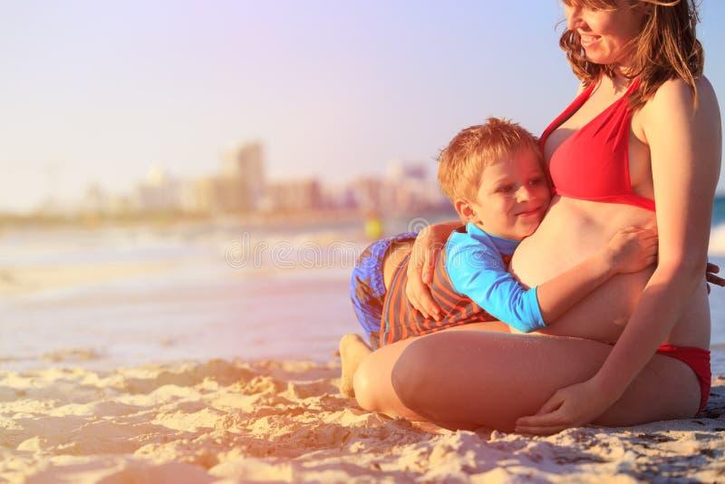 Kleiner Junge, der schwangeren Mutterbauch am Strand umarmt lizenzfreie stockfotos