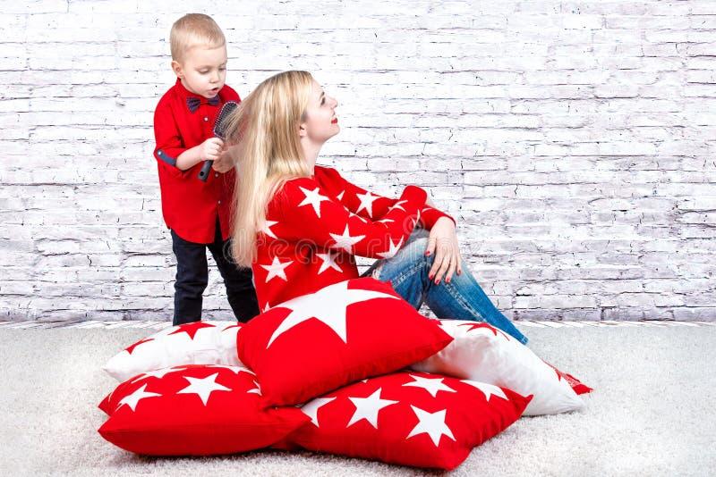 Kleiner Junge, der seine Kammmutter mit dem langen blonden Haar verkratzt Unter den weichen Kissen für die Hauptinnenverzierung stockfotos