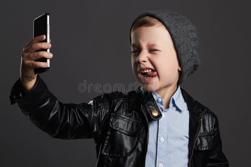 Kleiner Junge, der selfie tut stilvolles Kind im Ledermantel und im Hut Scherzt Gefühl lizenzfreies stockfoto