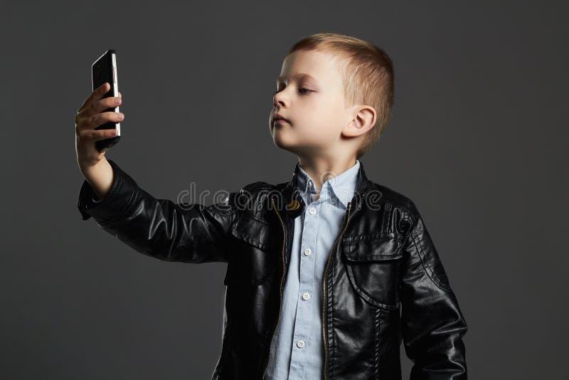 Kleiner Junge, der selfie tut stilvolles Kind im Ledermantel und im Hut Scherzt Gefühl stockfotografie