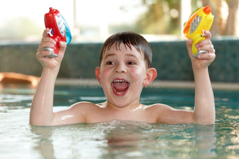 Kleiner Junge, der Spaß mit Wasserpistolen hat lizenzfreies stockfoto