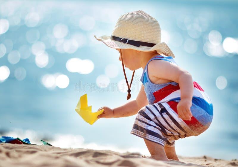Kleiner Junge, der am Strand im Strohhut spielt stockbilder