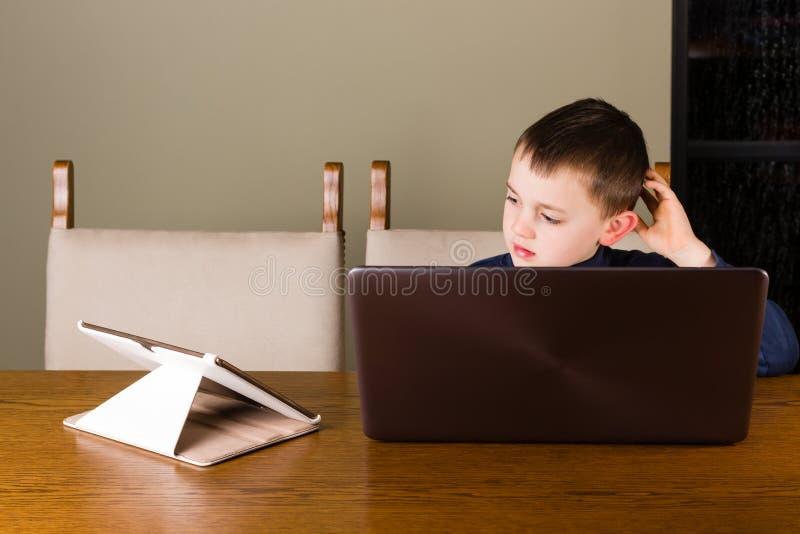 Kleiner Junge, der an Tablette und Laptop arbeitet lizenzfreies stockbild