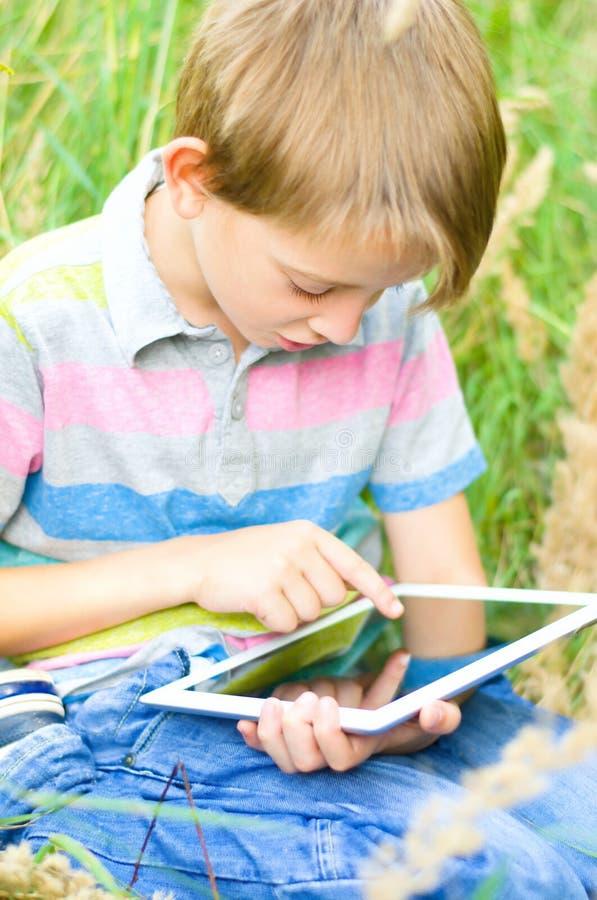 Kleiner Junge, der Tablette verwendet stockfotos