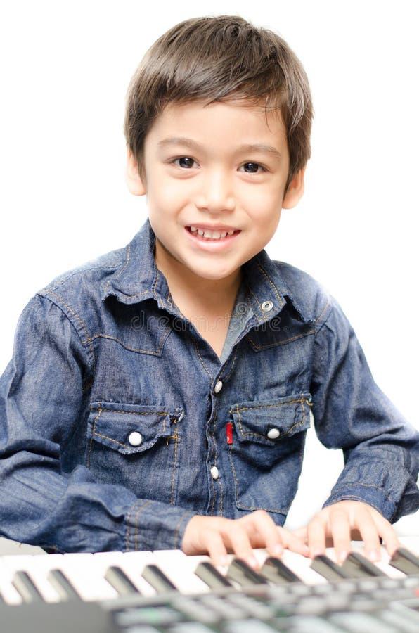 Kleiner Junge, der Tastatur spielt lizenzfreie stockfotos