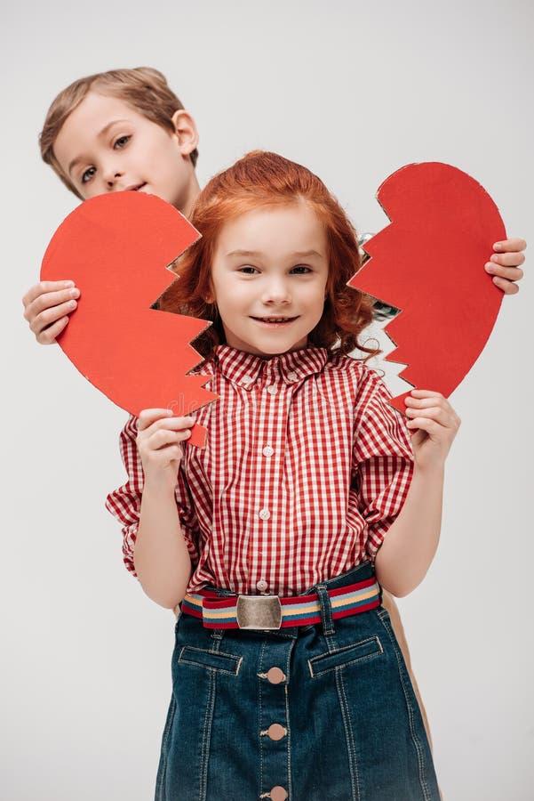 kleiner Junge, der Teile des defekten Herzens und entzückenden kleinen des Mädchens lächelt an der Kamera hält lizenzfreie stockfotografie