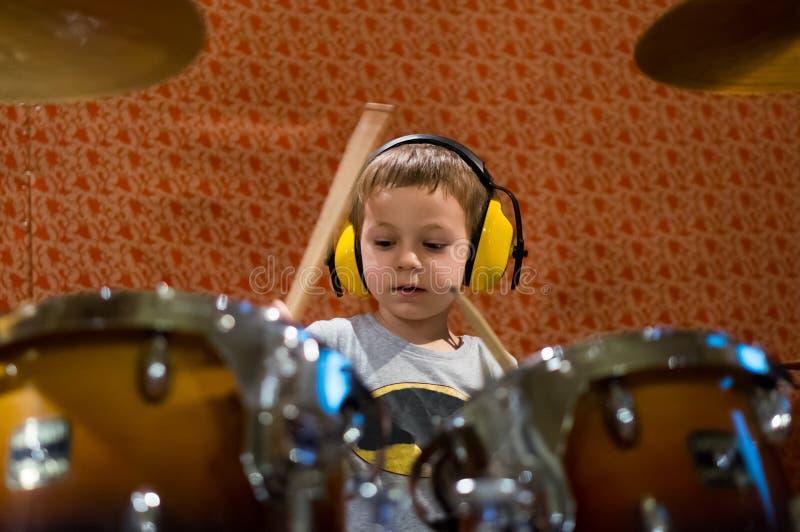 Kleiner Junge, der Trommeln mit Schutzkopfhörern spielt lizenzfreies stockbild