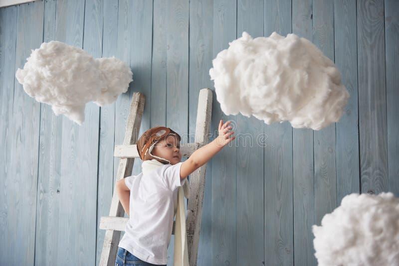 Kleiner Junge in der Versuchshutstellung auf der Leiter im Studio Reichweite zum Himmel Note das Wolkenkonzept stockfotos