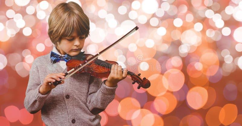 Kleiner Junge, der Violine über bokeh spielt lizenzfreie stockfotografie