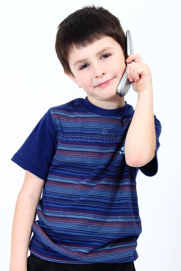 Kleiner Junge, der vom Handy benennt stockbild