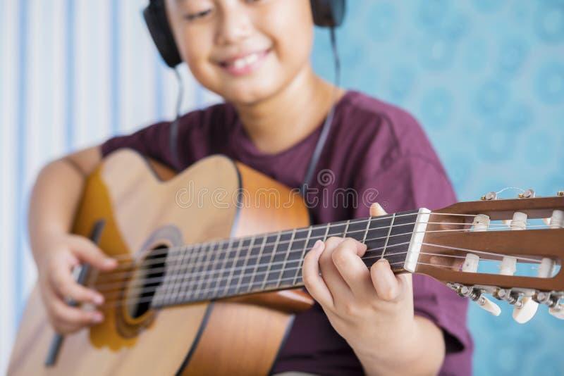 Kleiner Junge, der zu Hause Akustikgitarre spielt stockfoto