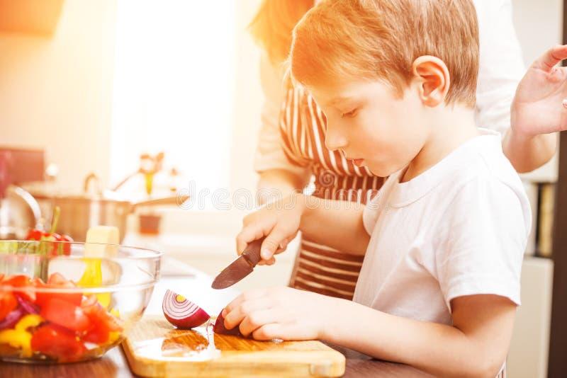 Kleiner Junge, der zusammen mit seiner Mutter kocht lizenzfreie stockbilder
