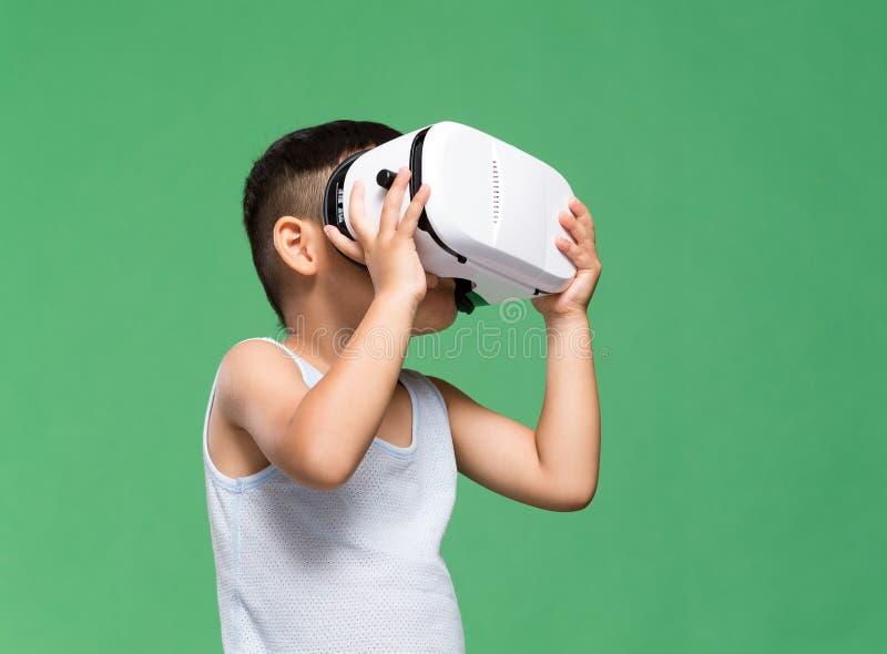 Kleiner Junge, der zwar Gerät der virtuellen Realität aufpasst stockbilder