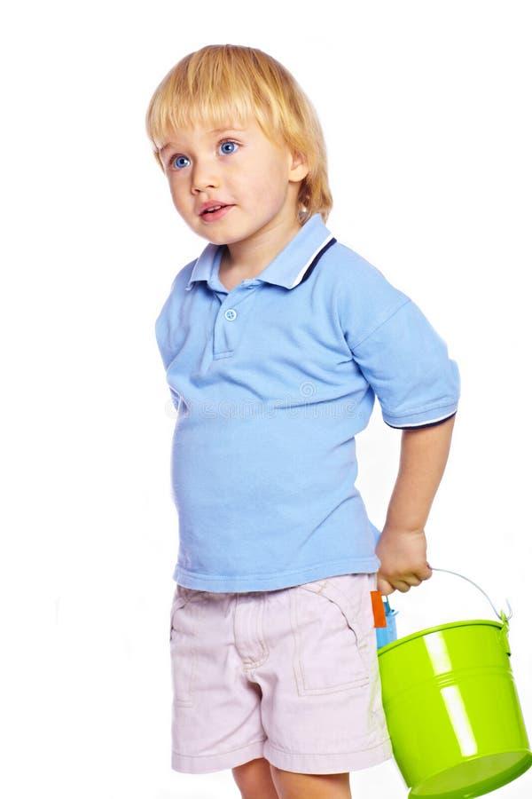 Kleiner Junge, der zwei Wannen anhält stockfoto