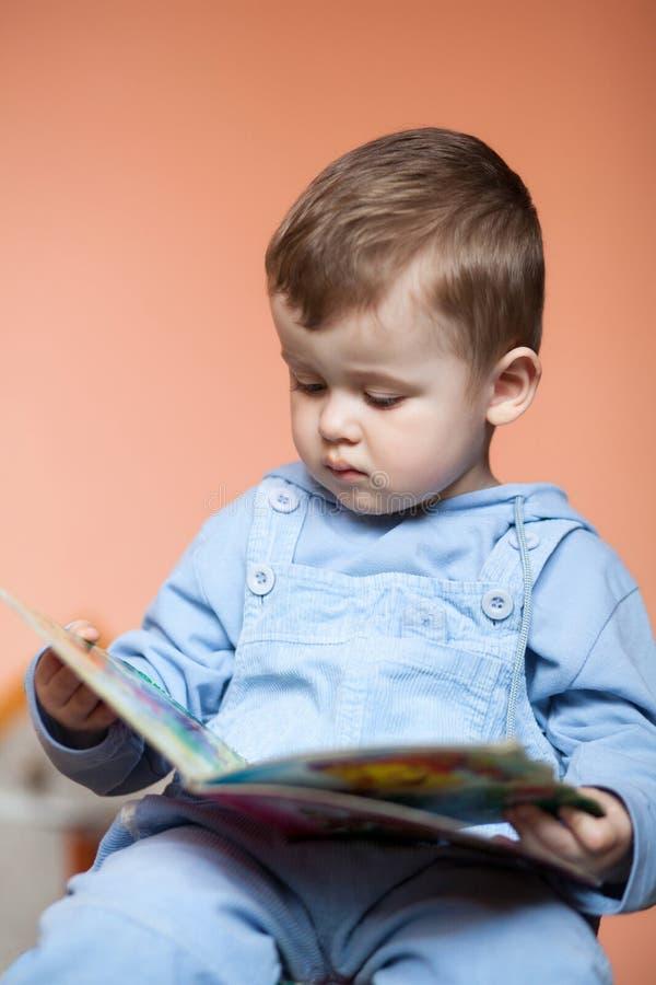 Kleiner Junge des Porträts mit einem Buch lizenzfreie stockbilder