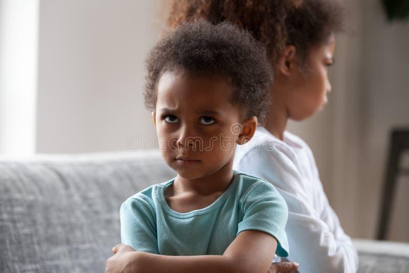 Kleiner Junge des verärgerten Afroamerikaners beleidigt, schwarze Schwester ignorierend lizenzfreie stockbilder