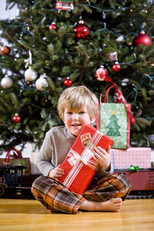Kleiner Junge durch Weihnachtsbaum-Holdinggeschenk lizenzfreie stockfotos