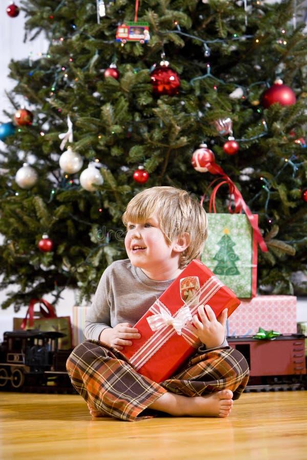 Kleiner Junge durch Weihnachtsbaum-Holdinggeschenk stockfotografie