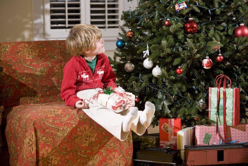 Kleiner Junge durch Weihnachtsbaum mit Geschenk im Schoss stockfotografie