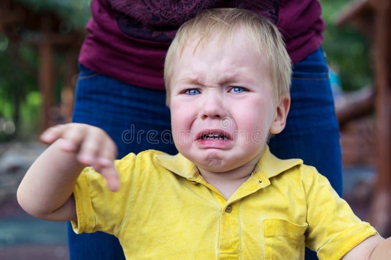 Kleiner Junge in einem gelben T-Shirt wird schlecht und Schreien gestört r lizenzfreie stockfotos