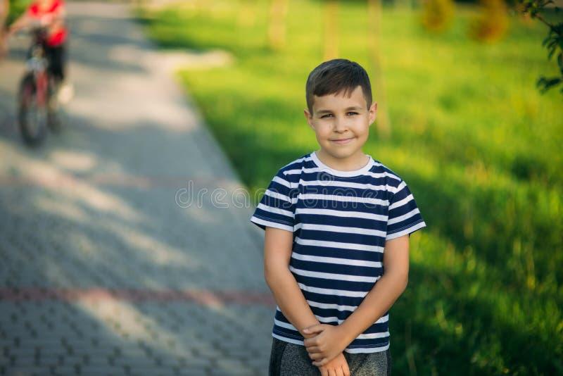 Kleiner Junge in einem gestreiften T-Shirt schaut durch Ferngläser Frühling, sonniges Wetter lizenzfreies stockfoto