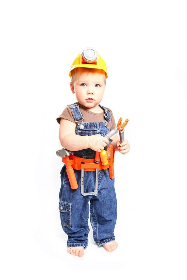 Kleiner Junge in einem orange Sturzhelm und Werkzeuge auf einem weißen Hintergrund stockfoto