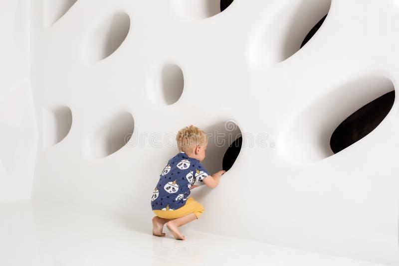 Kleiner Junge in einem T-Shirt und kurze Hosen auf einem weißen Hintergrund stockfotos