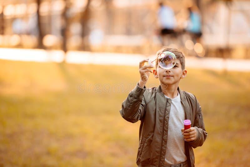 Kleiner Junge in einer Herbstjacke, die mit Seifenblasen spielt lizenzfreie stockfotos